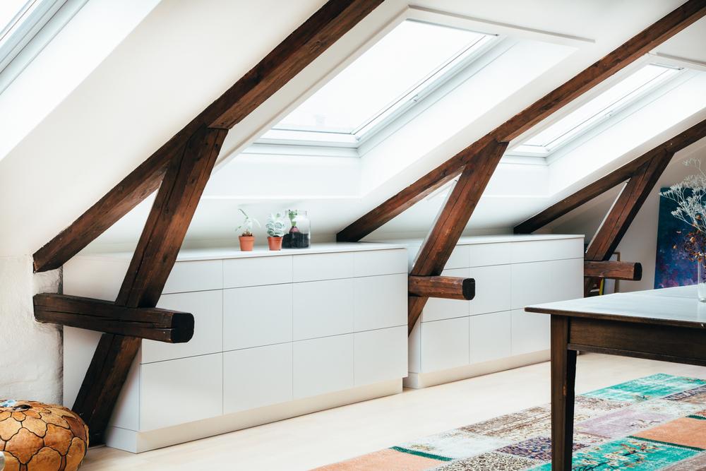 Integrerte hyller og skjenker tilpasset skråtaket og bjelkene er med på å frigjøre gulvplass og skaper en åpen atmosfære i leiligheten.