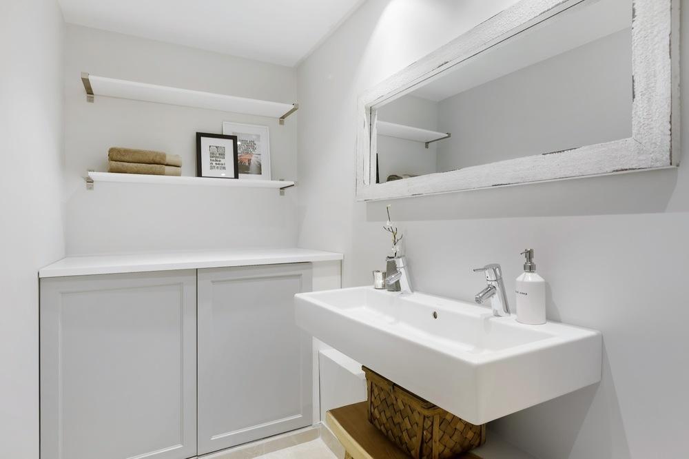 Baderomsbenken skjuler vaskemaskin og tørketrommel.