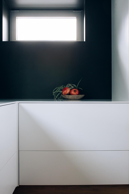 De gode lysforholdene fremhever de rene flatene på kjøkkenet og tillater en mørk farge på veggene.