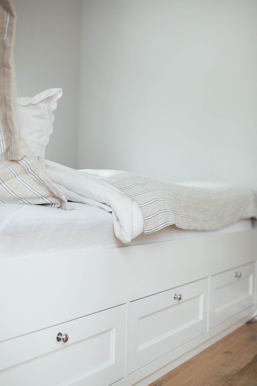 Skuffeløsning under sengen for oppbevaring av sengeteppe og pynteputer.