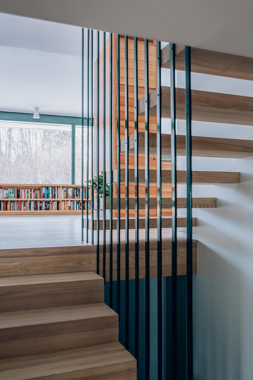 Trapp i hvitoljet eik. Det åpne rekkverket i stål får trappen til å se svevende ut og åpner opp mellom etasjene.