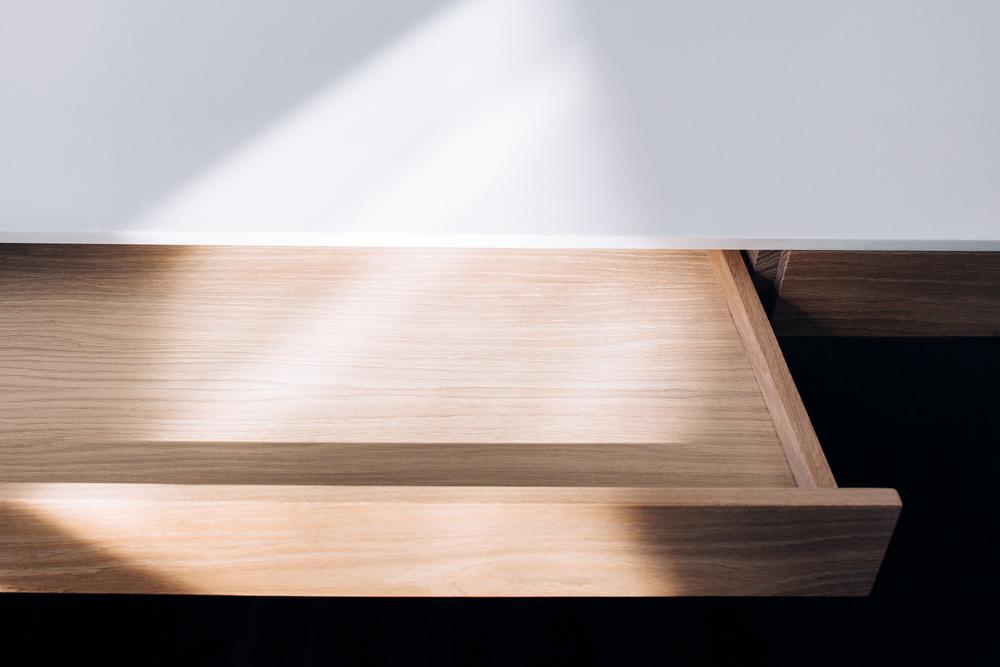 Disse  arbeidsbordet har mulighet for oppbevaring i skuffene under. Skuffene åpnes via innfreste håndtak som er skjult under.