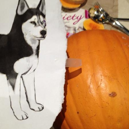 Transferring the image onto the pumpkin.