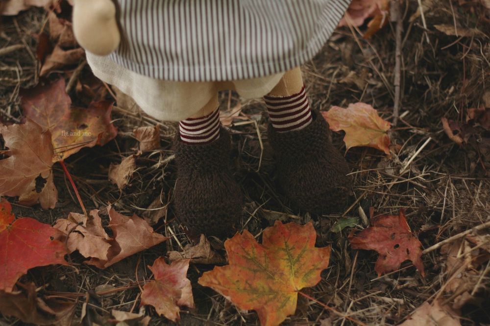 Feodora loves the crunchy maple leaves, with her knitted boots and her stripe socks. By Fig and me.