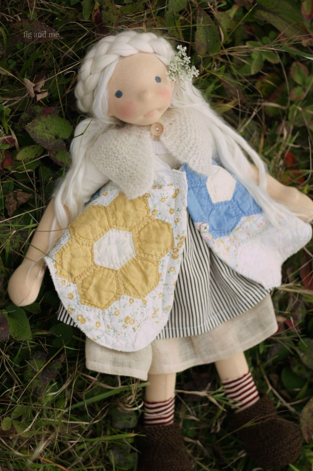 Feodora in her vintage hand-sewn hexagon quilt pinafore, wearing her cotton dress, her stripe socks and hand-knit boots, by Fig and me.