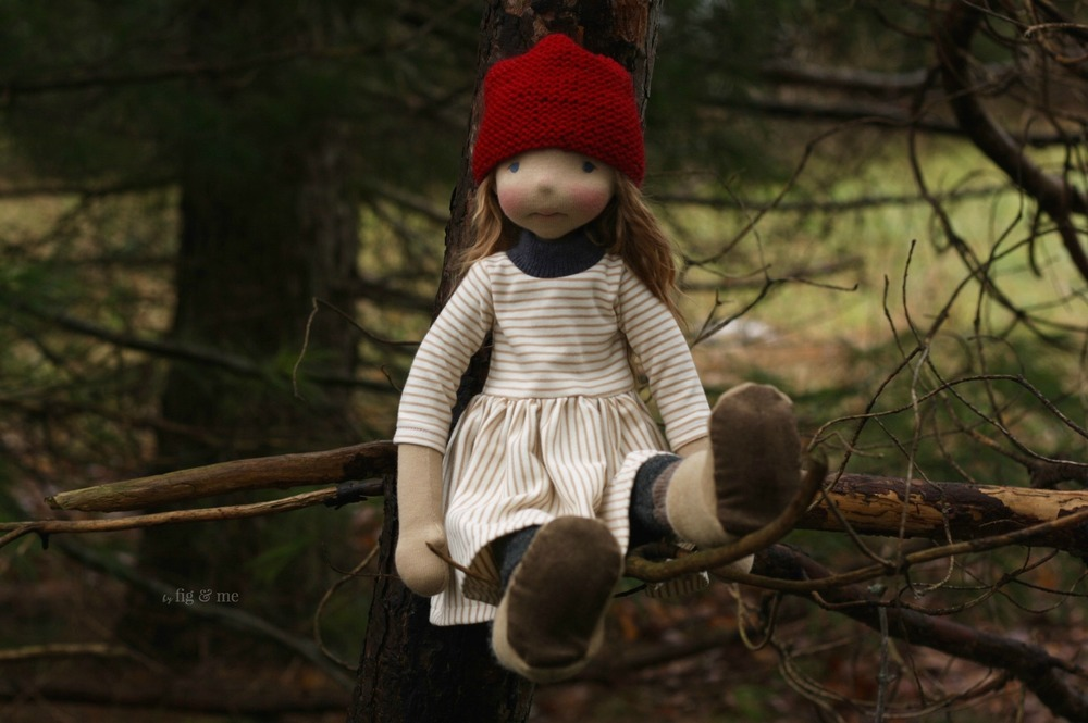 Sakasu, a natural fiber art doll, sitting on a tree. By Fig and Me.
