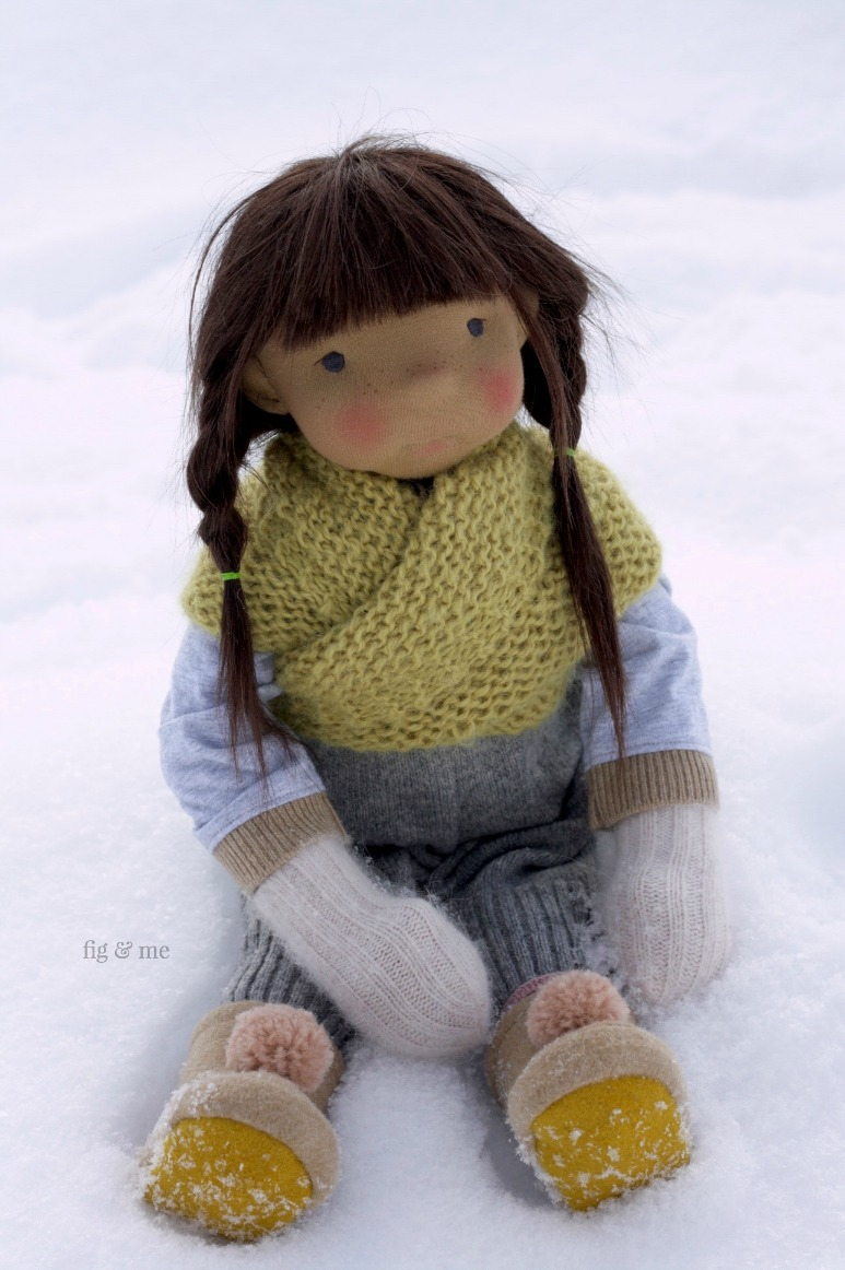 Ermentrude, a natural fiber art doll wearing handknitted shawl, merino overalls, pom pom mukuks and sweet braids. By Fig and Me.