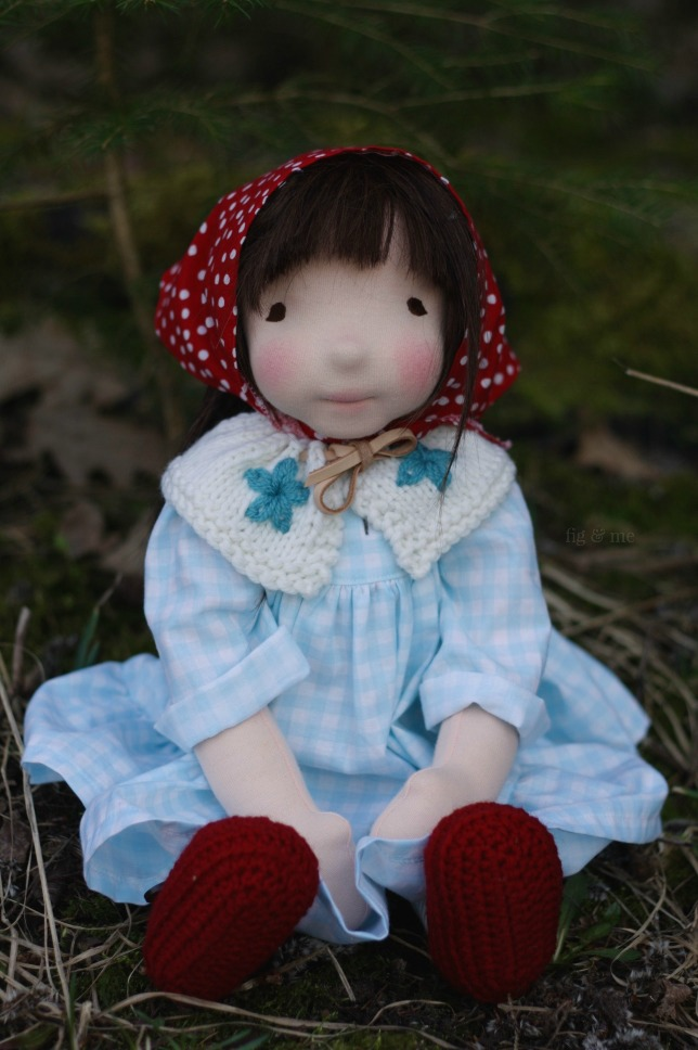 Imogen is a natural fiber art doll (waldorf inspired) wearing her blue gingham dress and red kerchief, by Fig and Me.