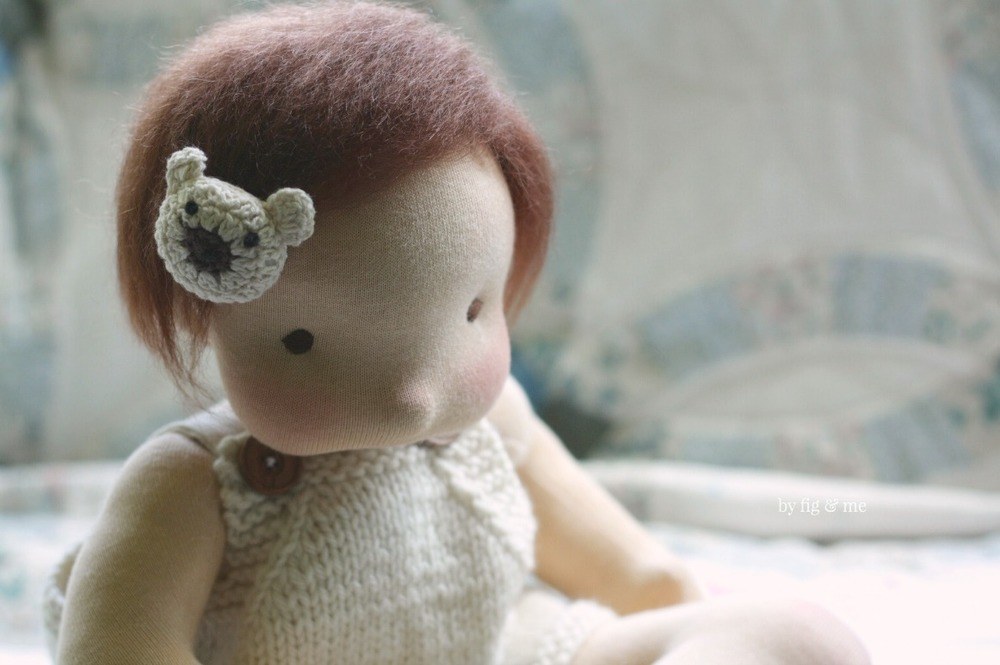 Baby Maia, showing off her bear barrette. Maia is a natural fiber art doll or waldorf  style doll, and made by Fig and Me.