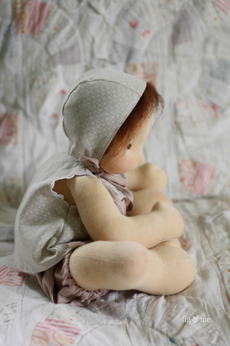 Baby doll Maia wearing her linen dotty outfit. A helmet-cap bonnet with self-fabric ties, an A-line top with ric rac and front patch pocket, and dusty rose bloomers with elastic casing. Doesn't she look cute in it?. I wuv her. By Fig and Me.