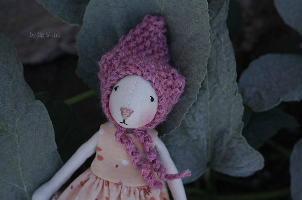 Cedar is a cloth doll and wears her hand knit wool bonnet, by Fig and Me.