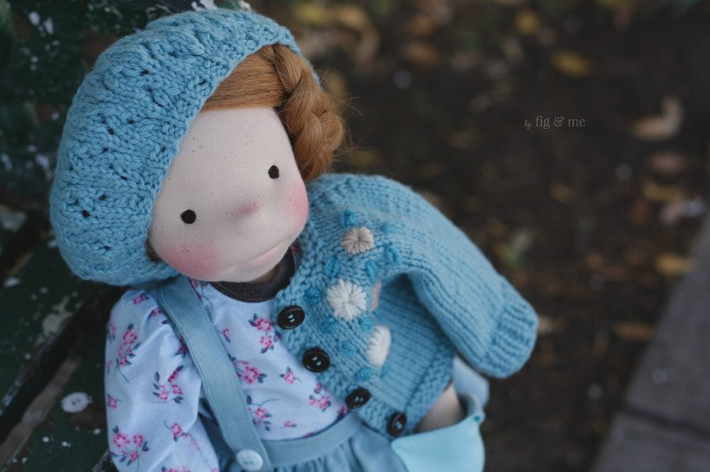 Pippa shows off her blue beret, with a sweet lace pattern and tiny ribbing + her matching cardigan with her customary four wooden buttons. By Fig and Me.