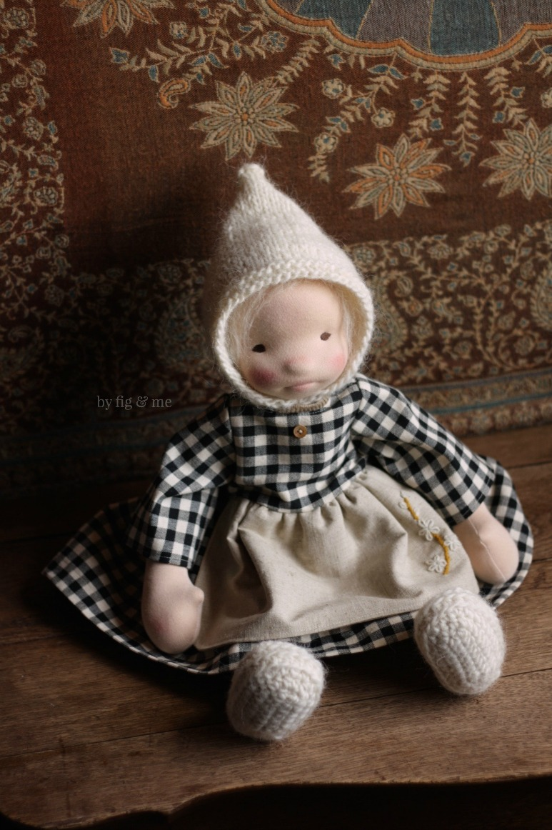Raisa wearing her thick cotton gingham dress, with linen apron and wooly hat. by Fig and Me.