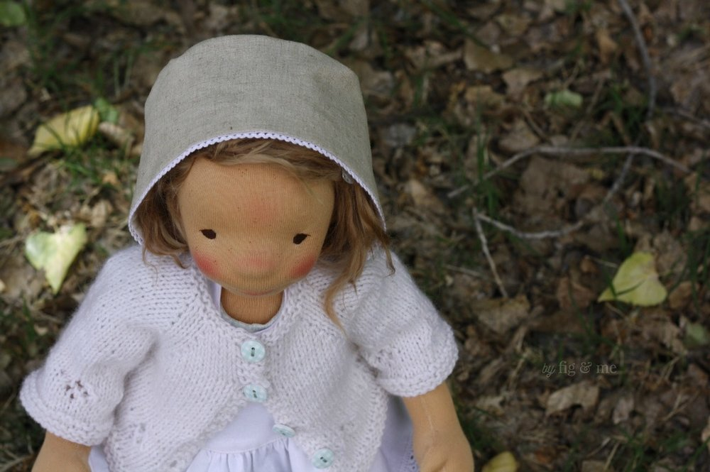 Little Ada, a natural cloth art doll by Fig and Me. Wearing her linen bonnet and her angora/cotton Spring cardigan.