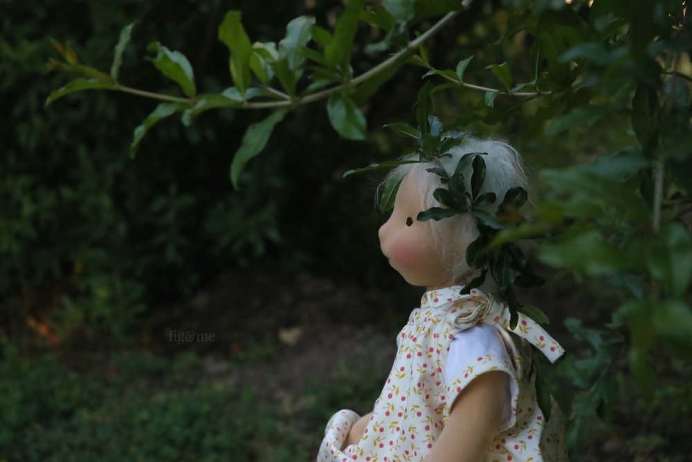Miss Romy in the garden, surrounded by pomegranates. Natural fiber art doll by Fig and Me.