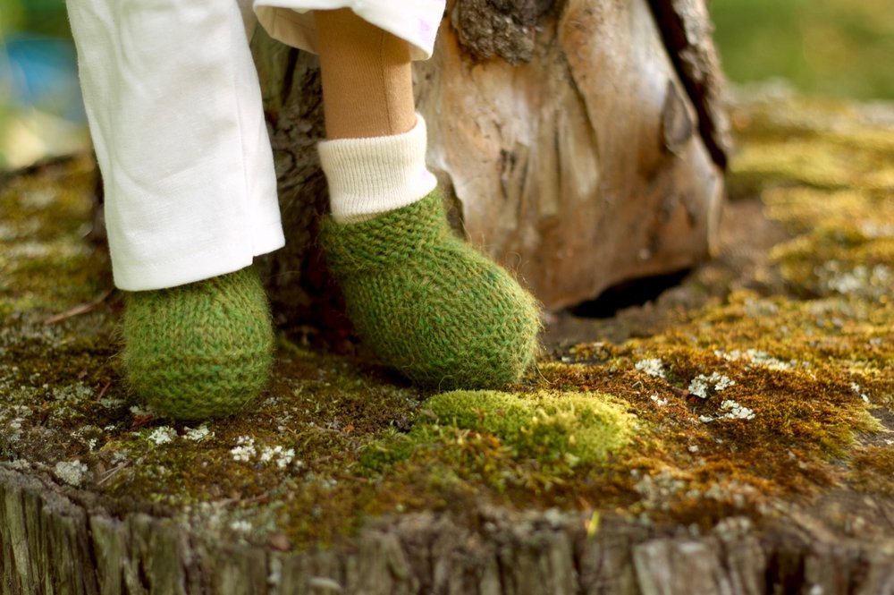 Little knitted shoes for Cedar, a cloth art doll. Stepping on soft mossy logs. By Fig and Me.
