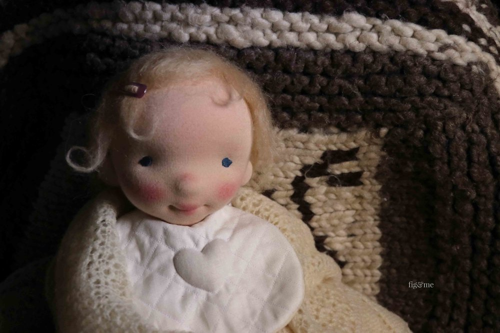 Baby Aelfreda is a custom natural fiber art doll, made by the loving hands of Fabs at Fig and Me. With her quilted bib, which has a lovely #trapunto heart. Made of linen and cozy flannel. #dollmaking