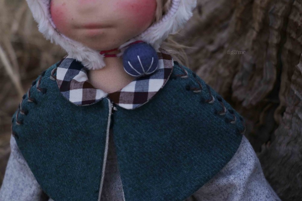 A vintage wool cape, with wool eembroidery. A wool felt bead for her bonnet and plaid peter pan collar on her wool flannel dress. Doll clothing details by Fig and Me.