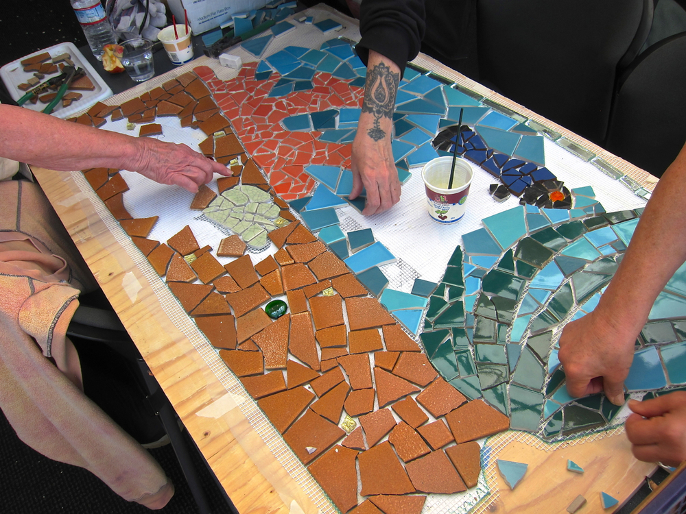 Participants set tile for 'Poolside Dreams' at UCSF Medical Center