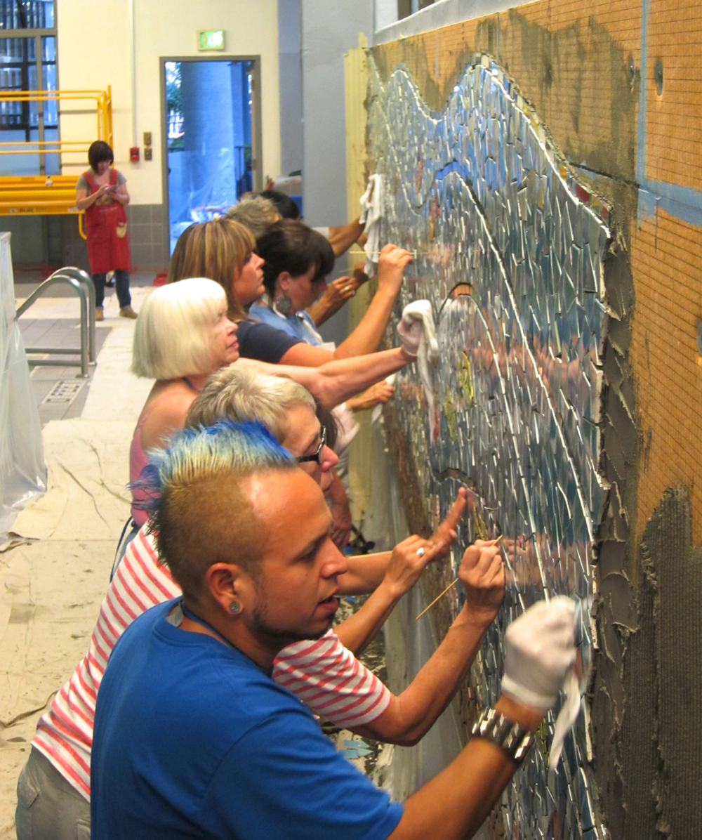 A large group of committed volunteers install the mural at UCSF.