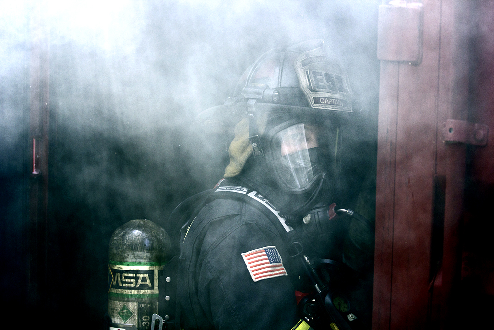 During a training for a firefighter certification course, a fire is lit in a shed to give trainees the opportunity to put it out in a controlled environment. Captain Robbins of the Mountain View Fire Department sits on the edge of the compound and closes the door when the fire needs to be built back up during the exercise at Fire Station Four in Mountain View, California, on May 4, 2015.