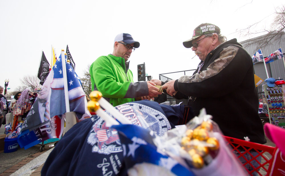 Billy Sewel (left), from New Mexico, buys a Trump baseball cap from Frank Maloney the day before the 2017 Presidential Inauguration, on January 19, 2017. Maloney came to Washington D.C. from Ohio to sell Trump merchandise to inauguration attendees. On Saturday, January 21, 2017, he would be selling paraphernalia at the 2017 Women's March.