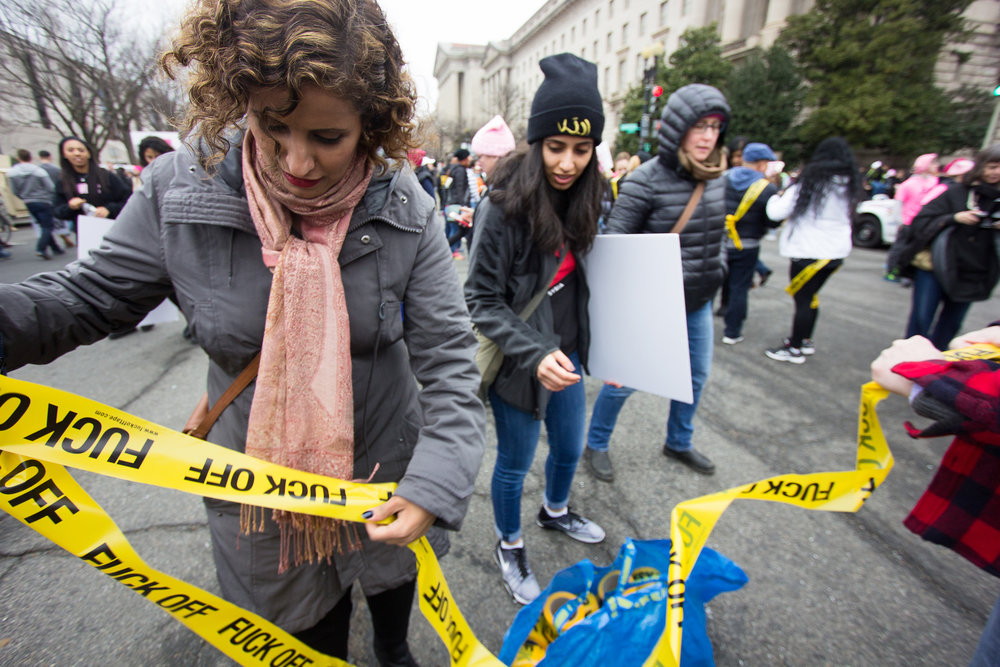 Rabyaah Althaibani, from New York, rips off a piece of crime tape to wear. The tape was made by artist Gabor Antallics (red flannel to right of photo) who is passing it out to protesters at the 2017 Women's March in Washington D.C. on Jan. 21, 2017.