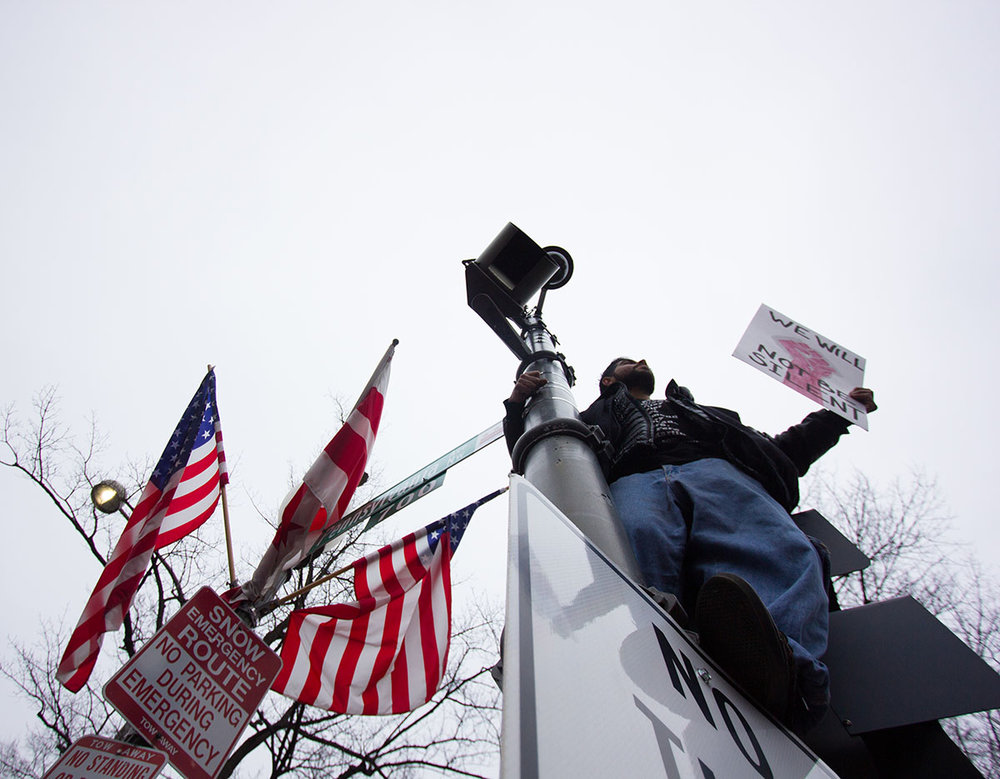 A man hangs from a post along Pennsylvania Avenue in Washington D.C. during the 2017 Women's March.