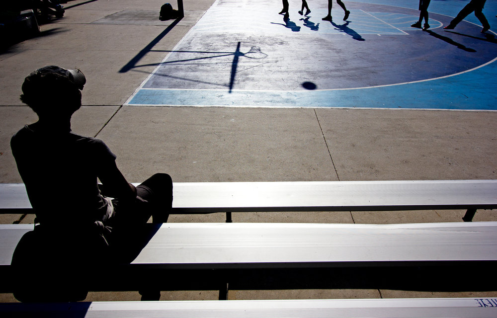 A man watches a game of pick-up basketball in Venice, California, on Aug. 21, 2018.