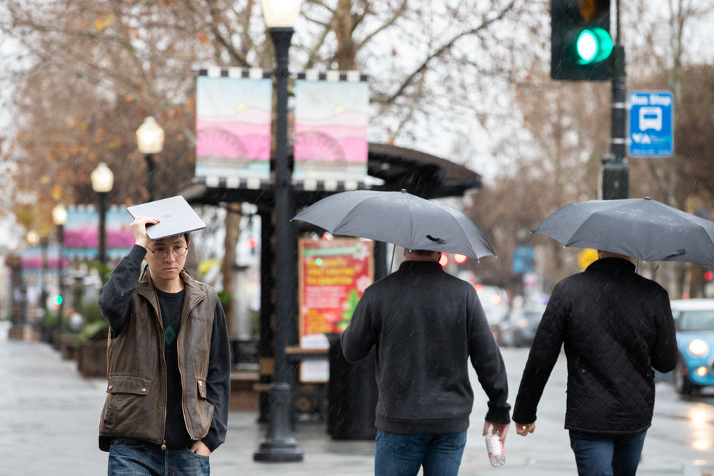 A man walking downtown in the rain on Castro Street in Mountain View, California, uses a MacBook Pro to keep dry on Jan. 15, 2019.