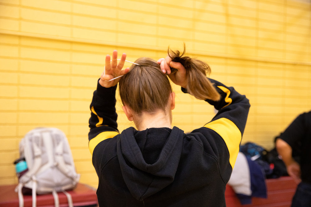 Paris Harrell ties up her hair in a ponytail before setting up the Mountain View High School big gym for a home meet against Homestead High School in Mountain View, California, on Jan. 31.