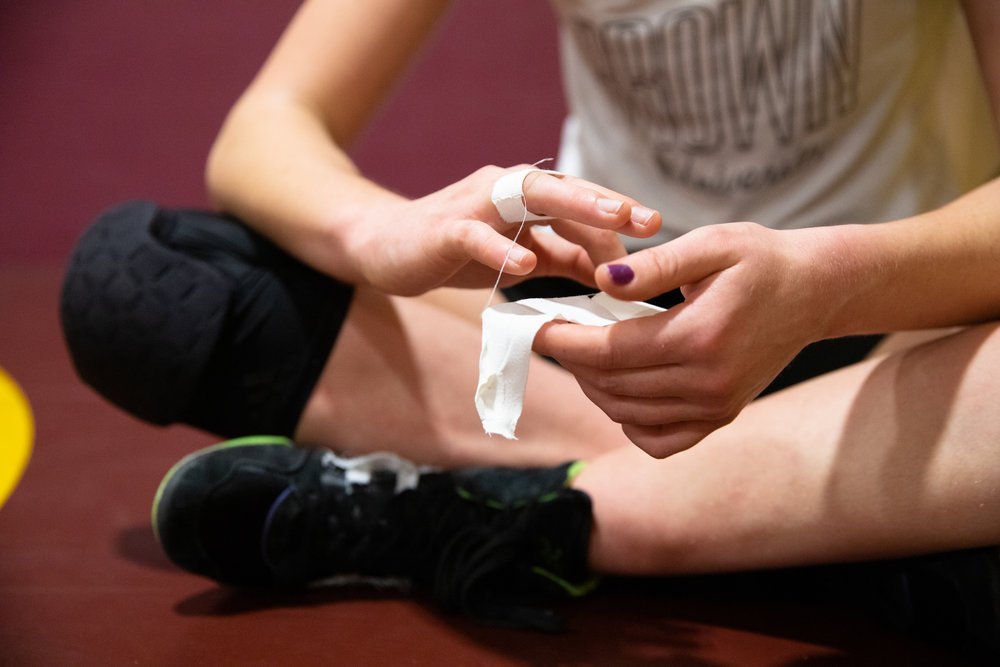 Paris Harrell secures her sprained ring finger to her middle finger in between fights during a practice for the CCS Championships in the Cupertino High School wrestling room in Cupertino, California, on Feb. 12.