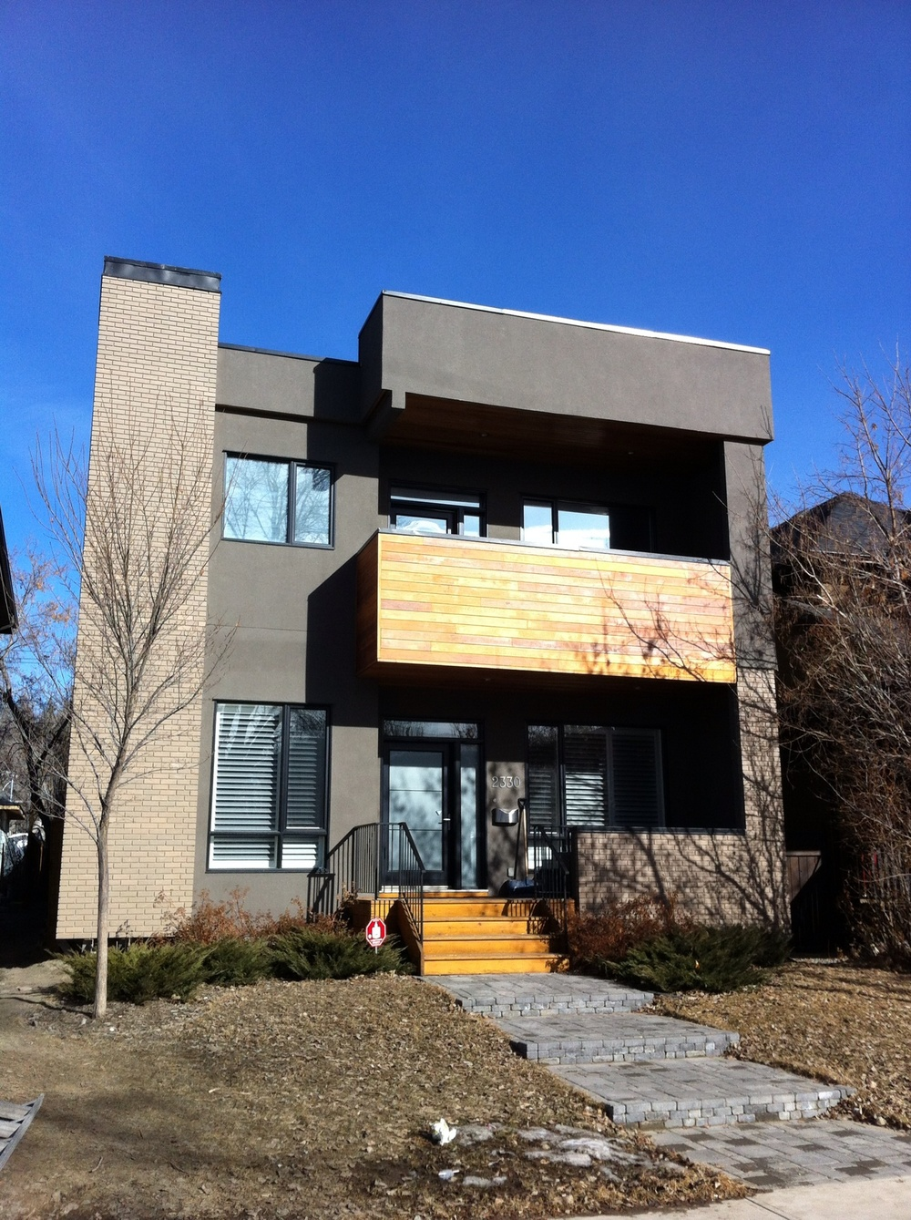 example of post modern home combining brick wood stucco that speaks to the future rather than the past