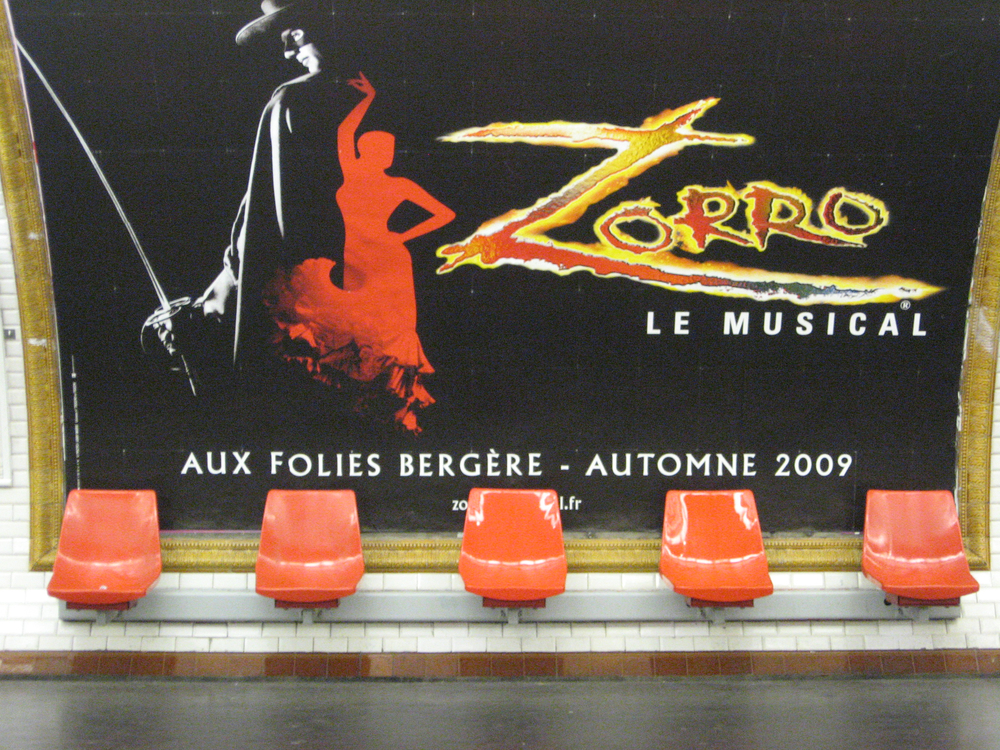 The Paris subway is like an art gallery with the posters being the art.  This could be an installation in a contemporary art gallery.  Did they purposely link the orange chairs with the poster.  Love how in Paris designers aren't afraid to use colour to create cheerful sense of place.
