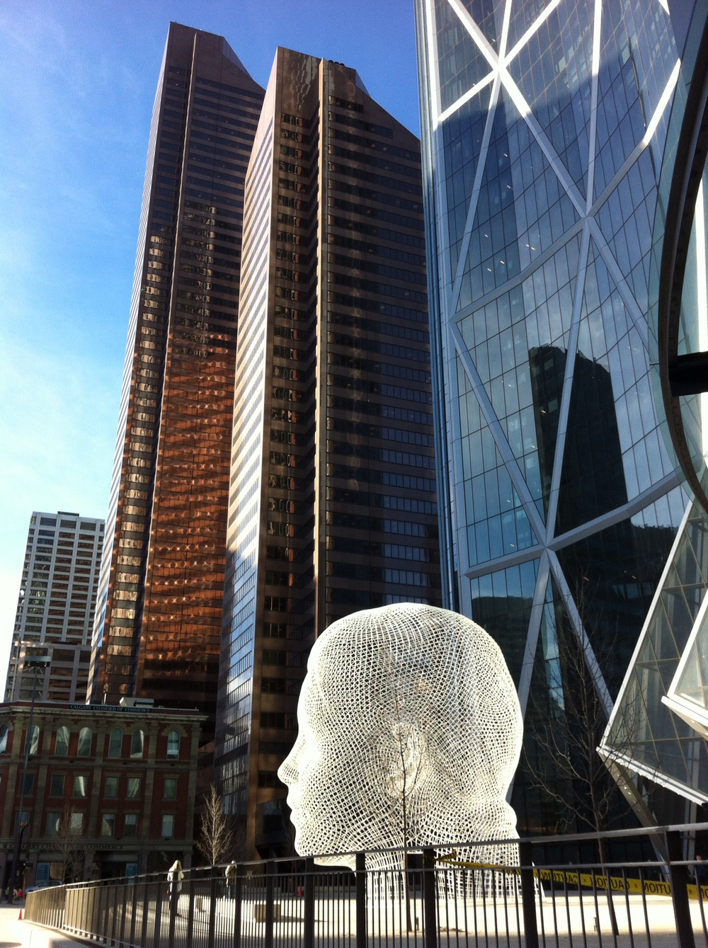 This photo captures the new Wonderland sculpture by Jaume Plensa on the plaza of the Norman Foster Bow Tower.  In the background is the Suncor Centre (built in the '80s), which consists of two towers the tallest one was the tallest in Calgary until the Bow was constructed.  The Suncor Tower has an interesting slanted roof top and the two towers together make a reference in their design to the iconic prairie grain elevator.