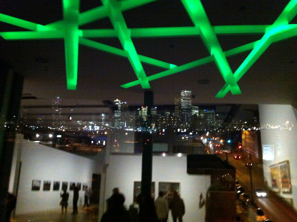 This photo is taken from the Esker Art Gallery which is located on the eastern edge of the Centre City.  The downtown skyline can be seen in the background.  Like the SAIT campus buildings there is a lot of use of neon sticks in the ceilings of the gathering spaces.  Both were designed by the same Calgary architectural firm Kasian.