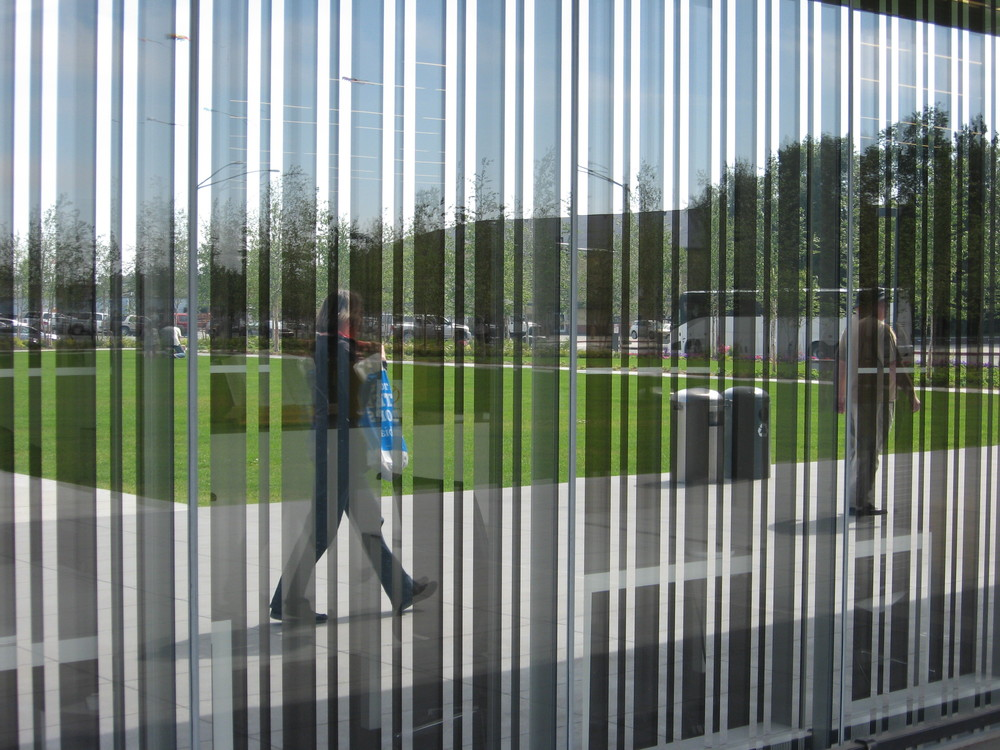 I captured this image of someone walking past the Anchorage Museum. The facade of the museum is made of a reflective material that captures the people milling about the front lawn creating fun works of modern art.