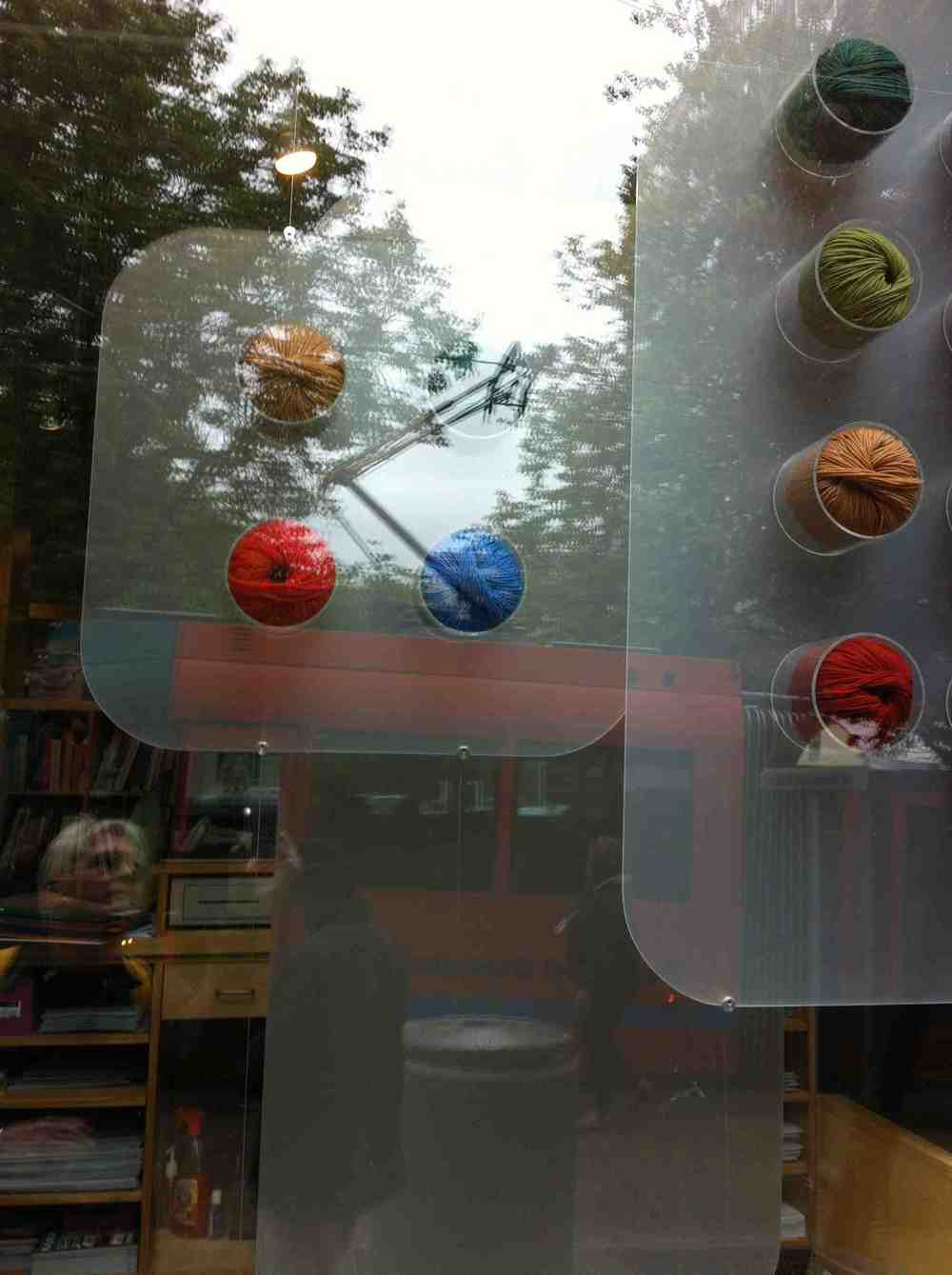 Found this window with fun colours of yarn displayed in a cool quirky manner that is made even more fun with the reflections of various people wander the street and getting on the bus.  Flaneuring at its best.