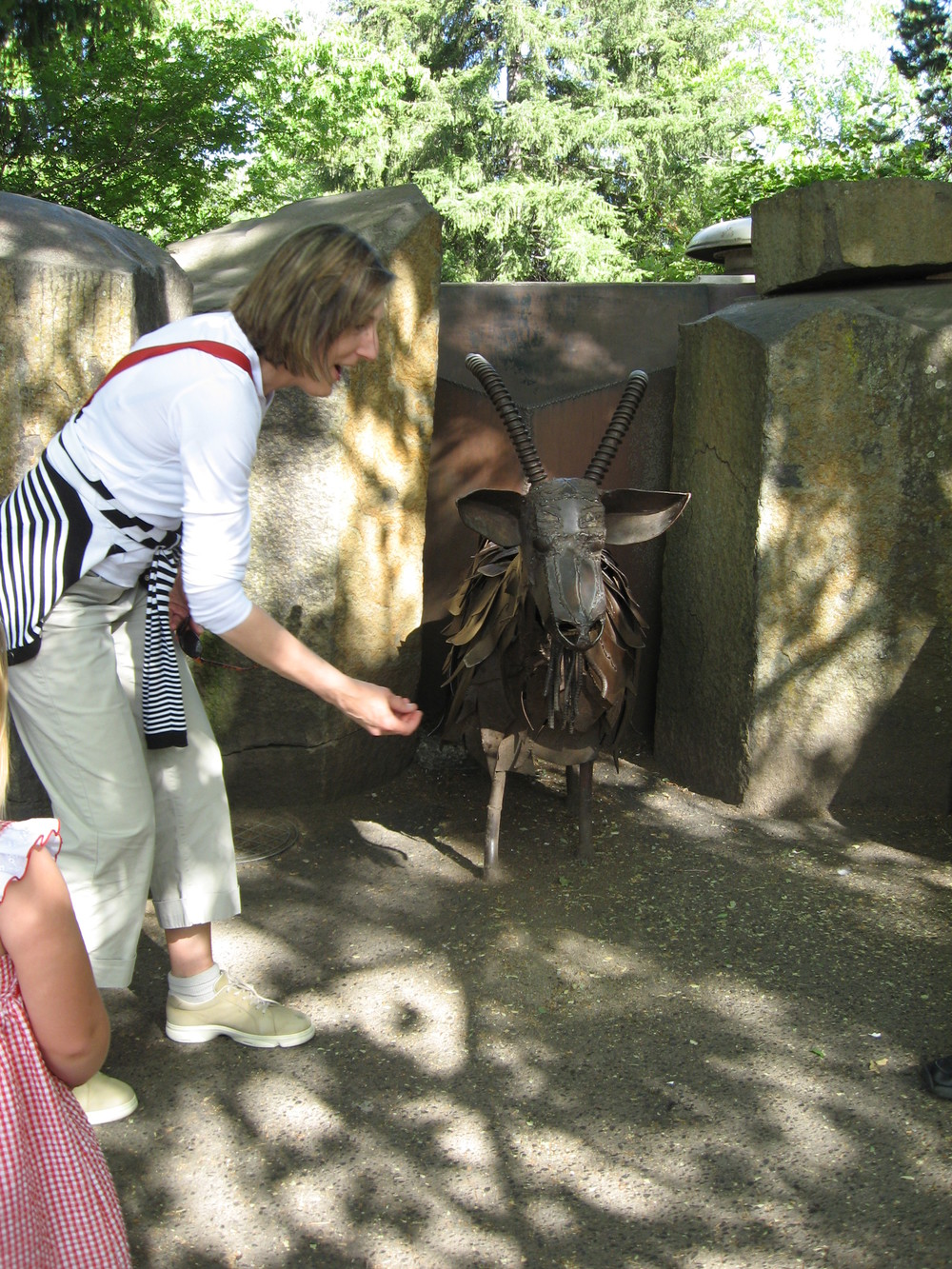 "Brenda feeding the ""Garbage Goat"" while young friend watches."