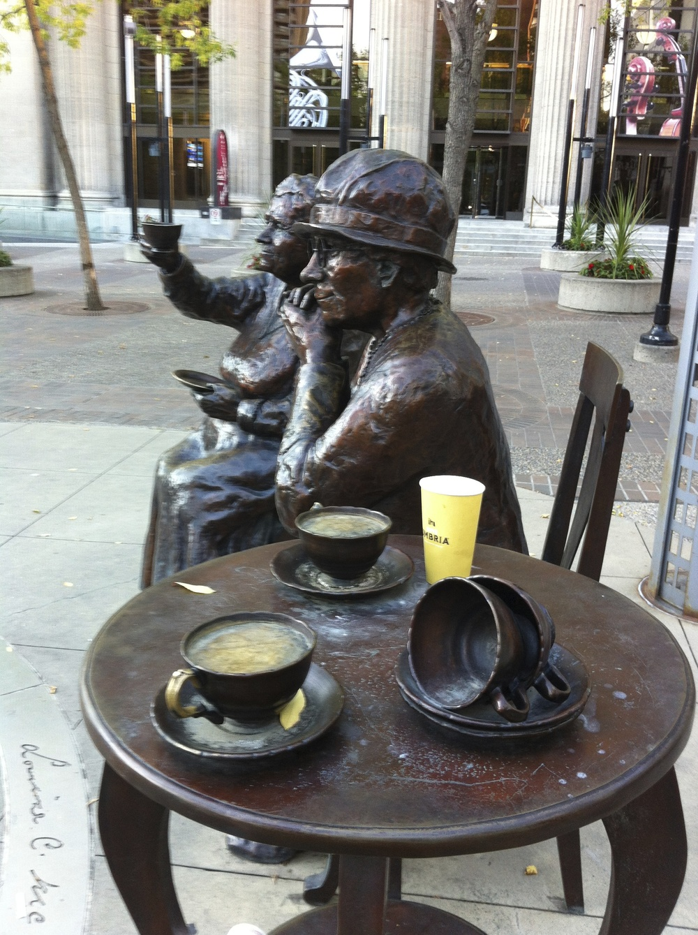 Henrietta Muir Edward sits next to McKinney holding up her cup of tea as if she is toasting the victory.  People love to interact with the sculptures often leaving their coffee cups or other artifacts on the table.