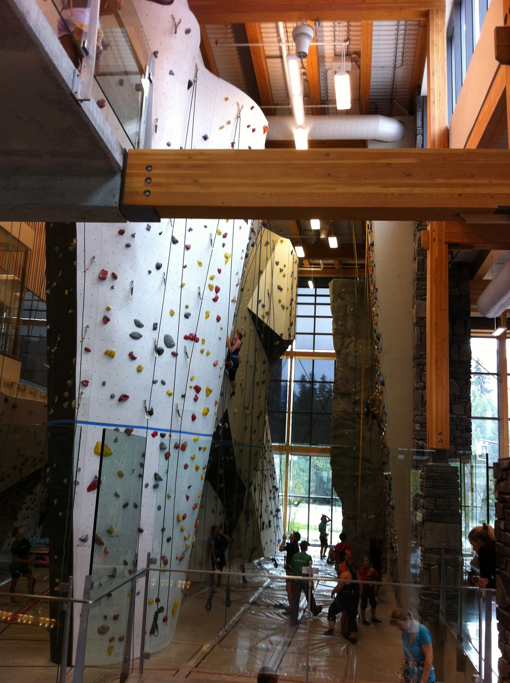 The climbing wall located on the main floor of the new Canmore, Alberta recreation centre bears a striking resemblance to an office lobby with its two floor open ceiling. Sure beats a sterile office lobby for animation.