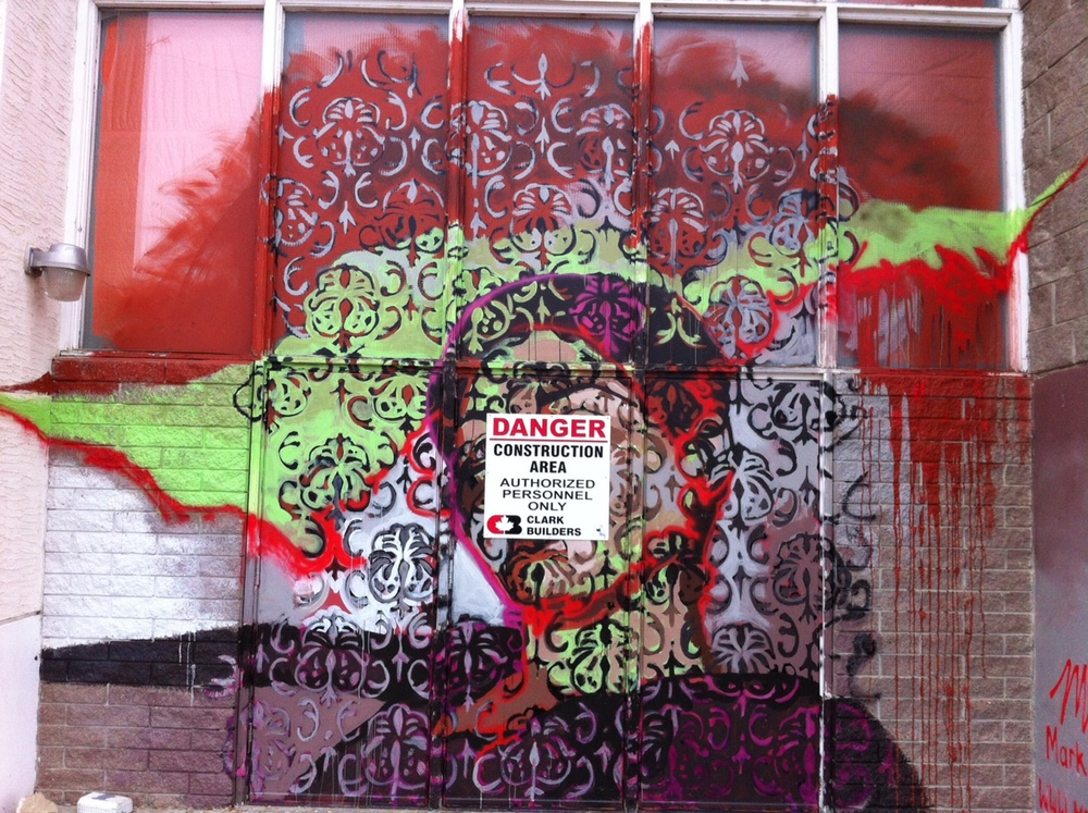 Mural next to the large box addition at the school entrance.  Love how the artist has used the Danger sign to mask the face. Is this a Danger Mask?