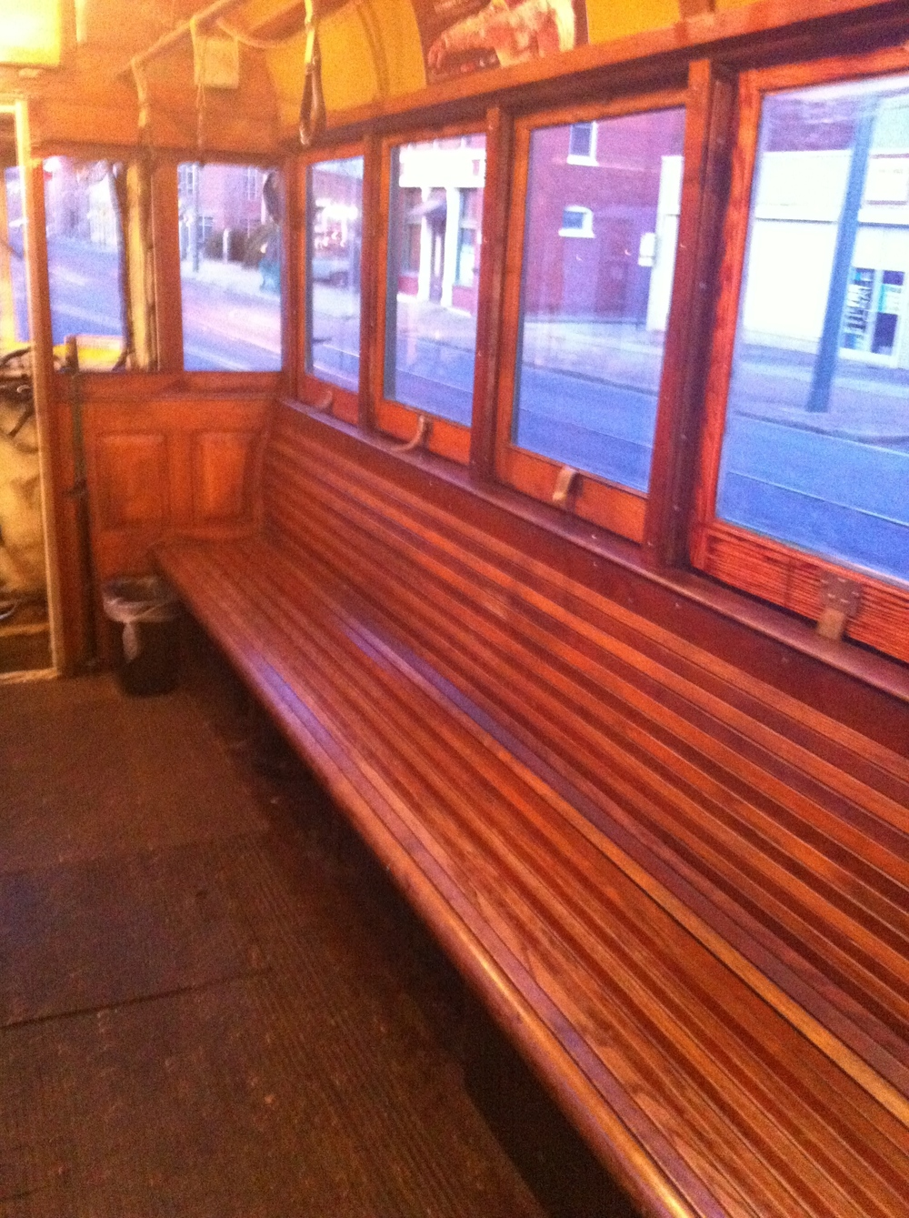 Inside the trolley are long wooden benches or small single seats.