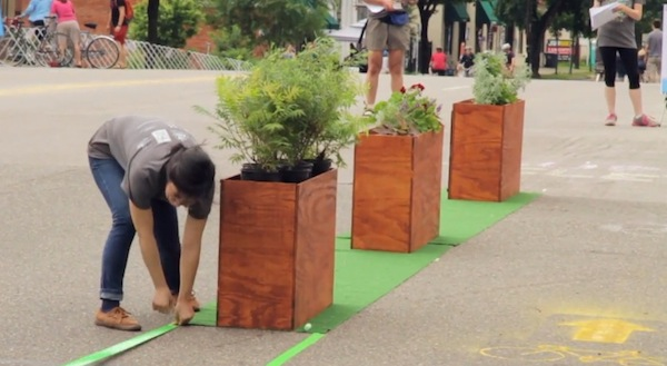 Simple plywood planter were created with plants as the barriers between the road and the bike lane. (Photo Credit: Tree Hugger).