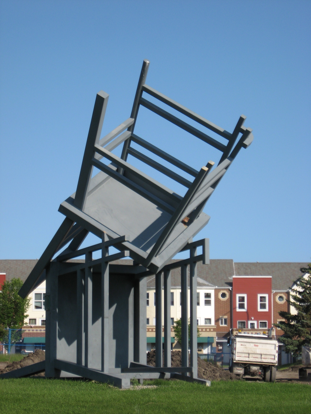 Homage, by Derek Besant (1989 is a 20 foot by 18 foot by 10 foot sculpture located on the campus of Mount Royal University, in Calgary.
