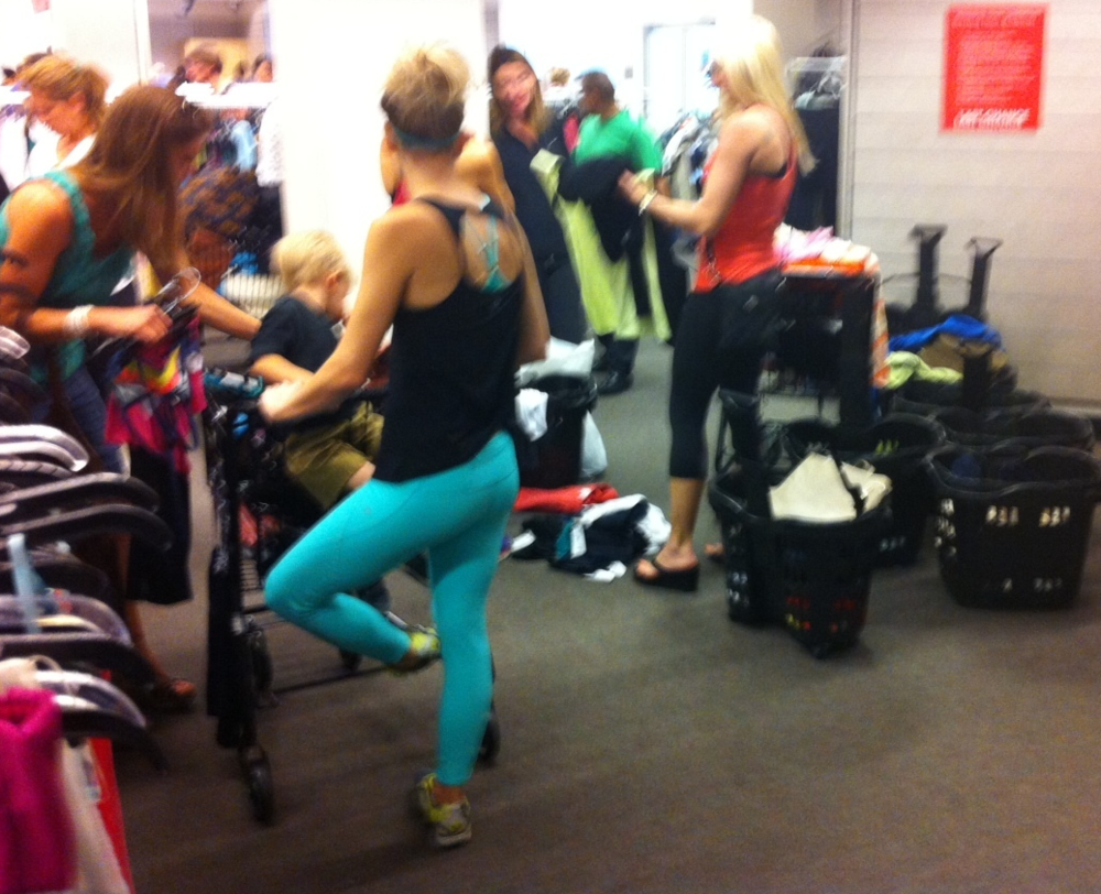 In another corner, the yoga women can't wait for the dressing room so they are trying on clothes over their own clothes.