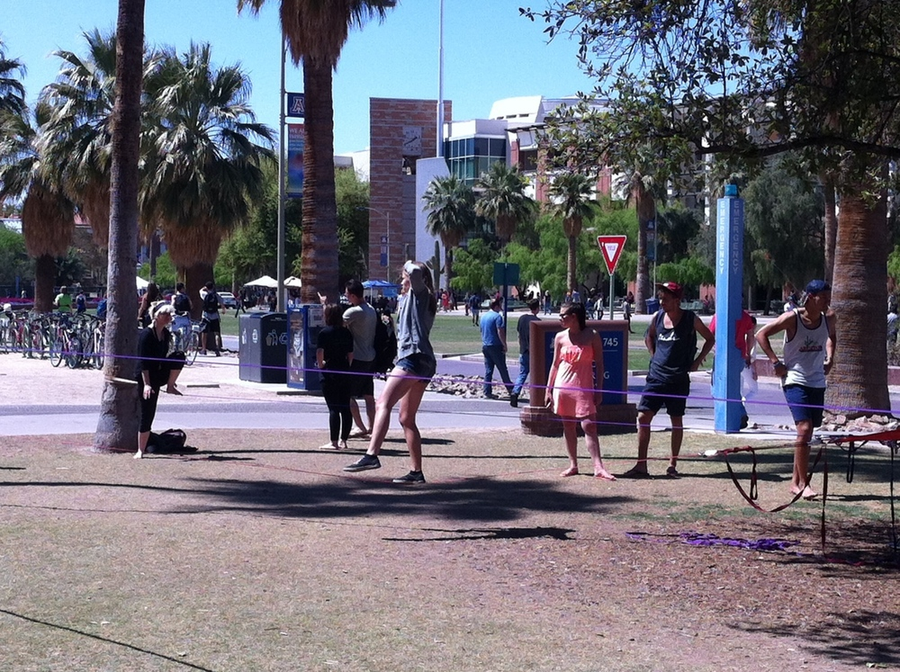 The central pedestrian mall is a beehive of people moving from building to building.   With the palm trees and sand, the only thing missing is the water. Students had set up three slack lines that made for a circus-like atmosphere. The UofA's Central Mall is the Champs-Elysees of university campuses.