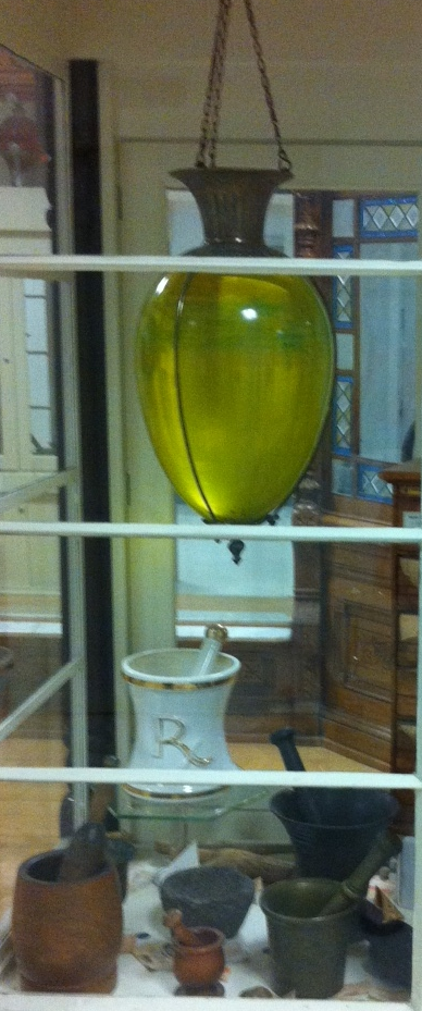 "The use of show globes (like this yellow glass one) dates back four centuries as a symbol of pharmaceutical and medical care. Sailors landing in English ports knew that a show globe in a store window meant medical treatment was available there.  In America, a red show globe could mean the town had some kind of quarantine or disease while a green one indicated the town was healthy.  Dick Wiedhopf, Curator, History of Pharmacy Museum, informed us in an email that ""pharmacists took great pride in creating colours for their show globes. There are several books on how to make these colours, but today we use common food colouring. The yellow colour has not meaning, other than it is attractive."""