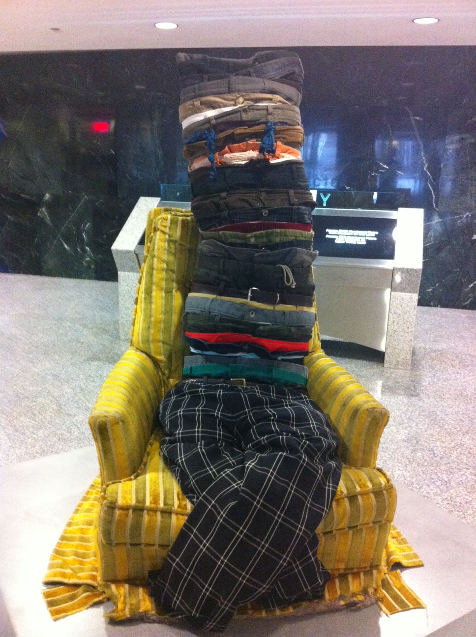 "Owen Gordon's ""Waisting Time"" is a quirky artwork that incorporates lots of pants, belts and a chair."