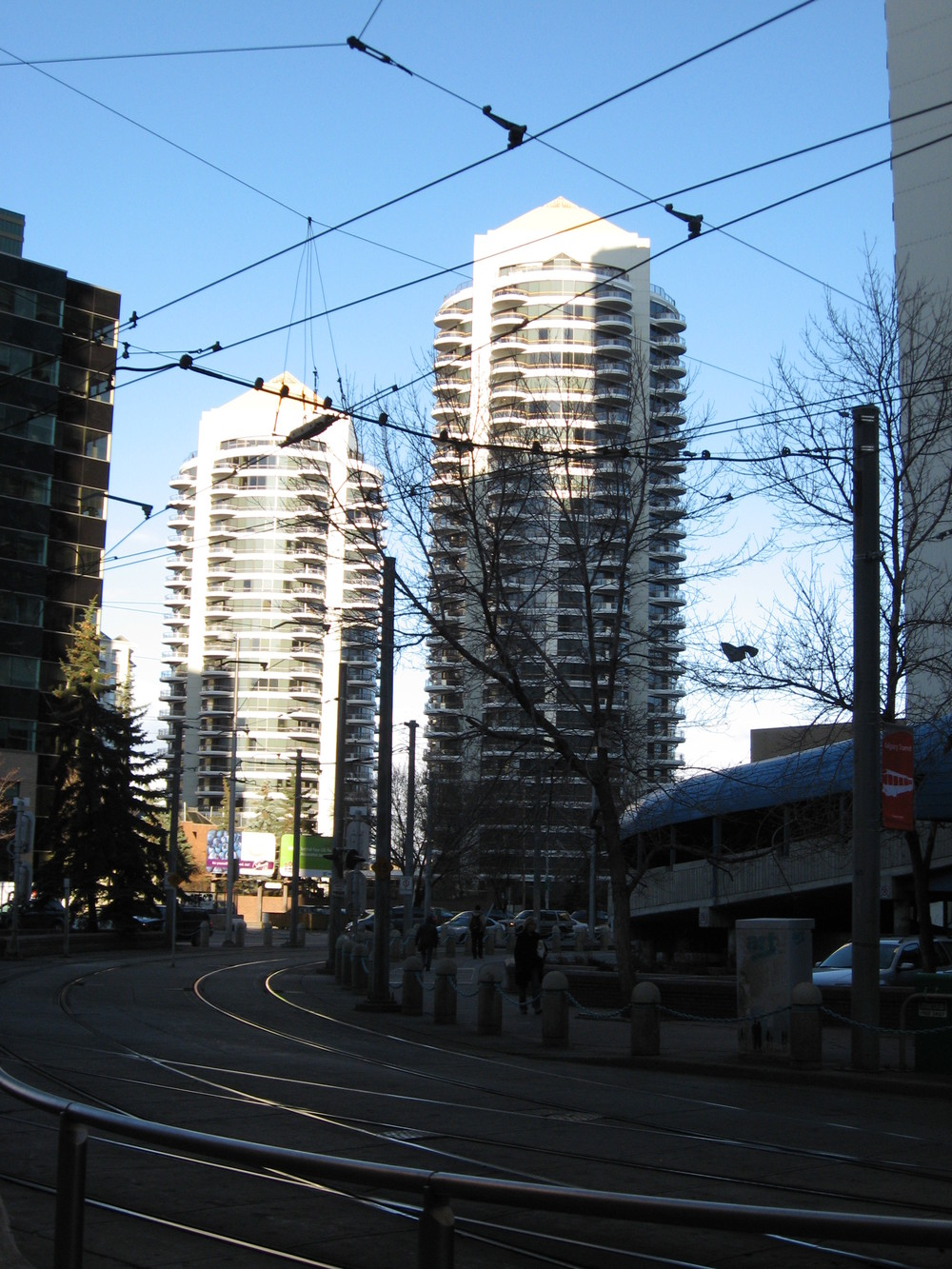 Even on a bright day, office and condo towers cast shadows on the street that make it look dark and unattractive.  Railway tracks and barriers make it difficult to walk across the street.